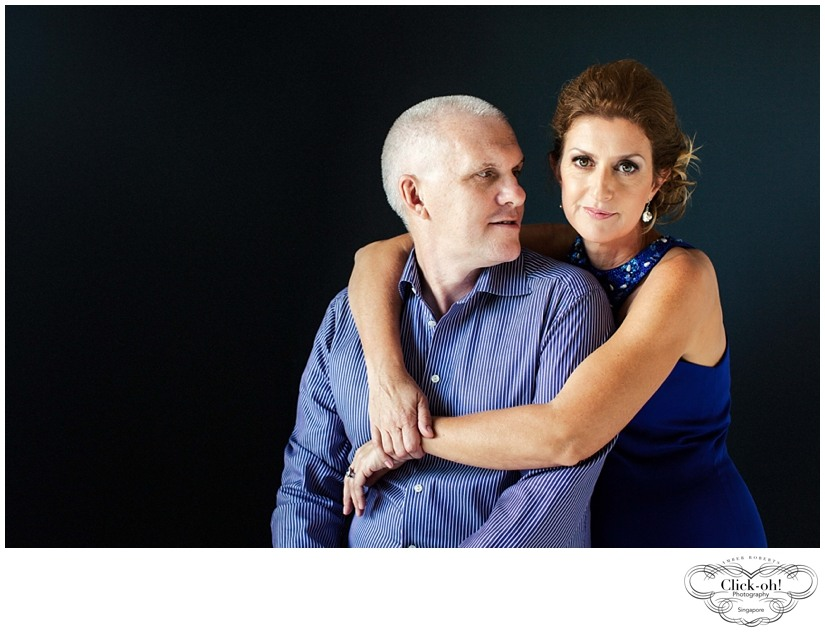 glamorous couple in blue embraces in studio photo