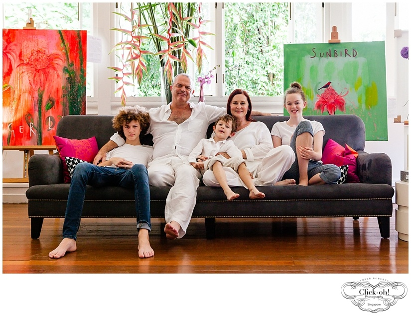 family of 5 relax on sofa surrounded by paintings