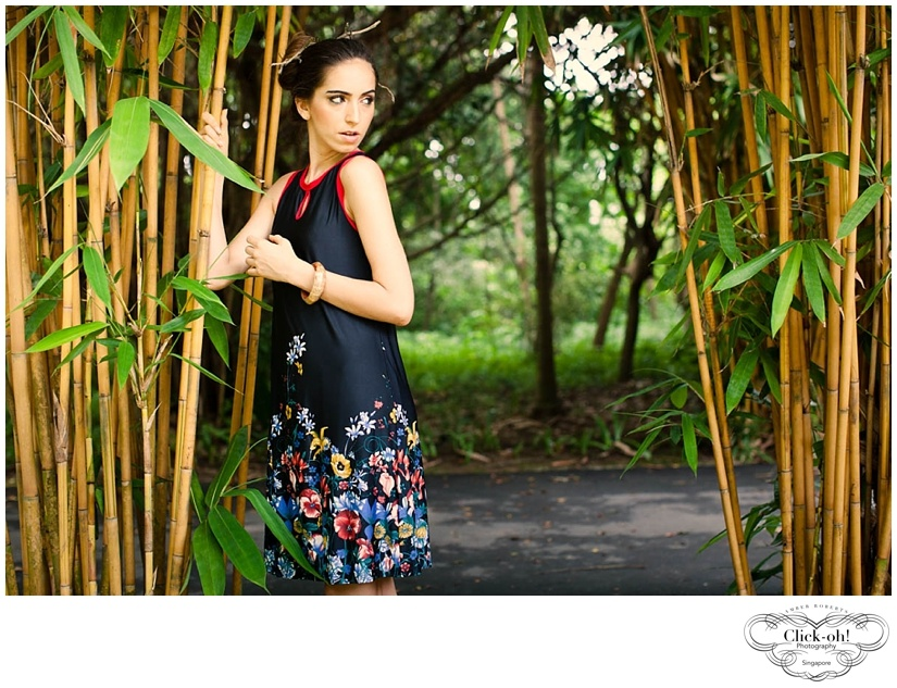 model wearing dress poses with bamboo