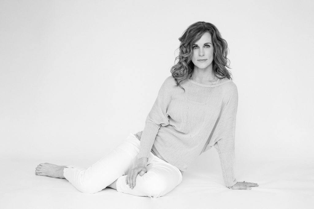 black and white portrait of woman sitting on floor during photo shoot