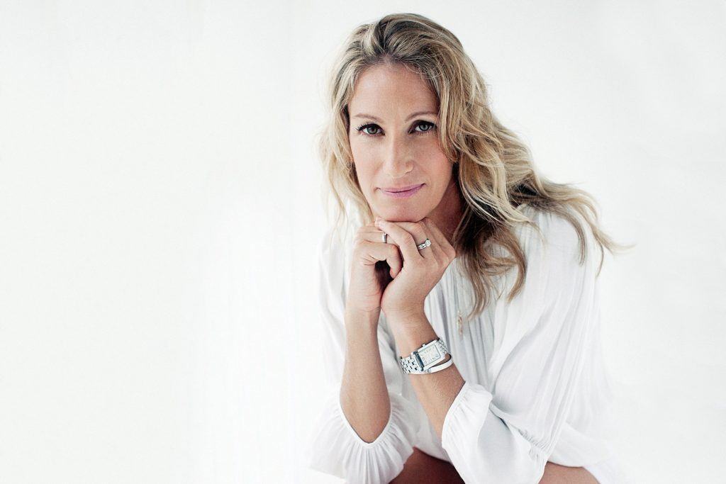woman wearing white blouse sits comfortably during contemporary photo session