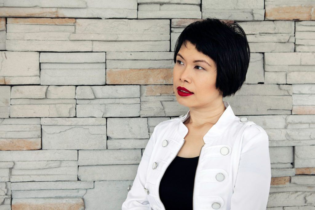 Woman leans on wall during personal branding photo session Geneva