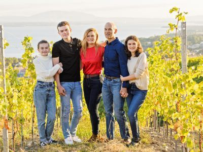 Family standing in vineyard at golden hour