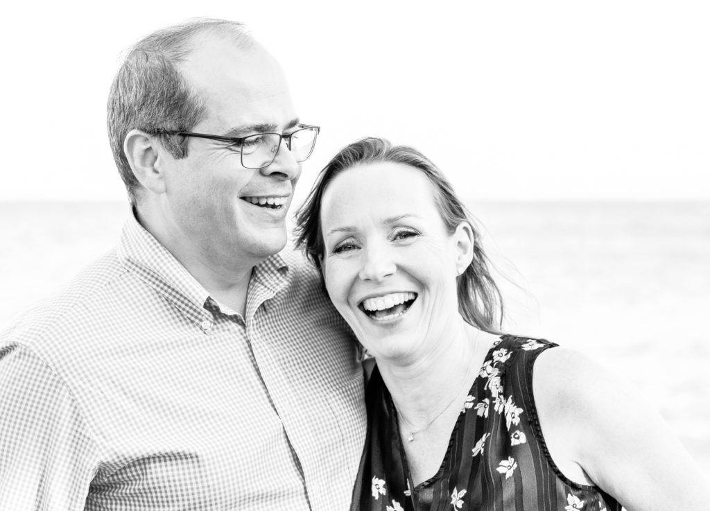 black and white portrait of laughing couple by lake geneva
