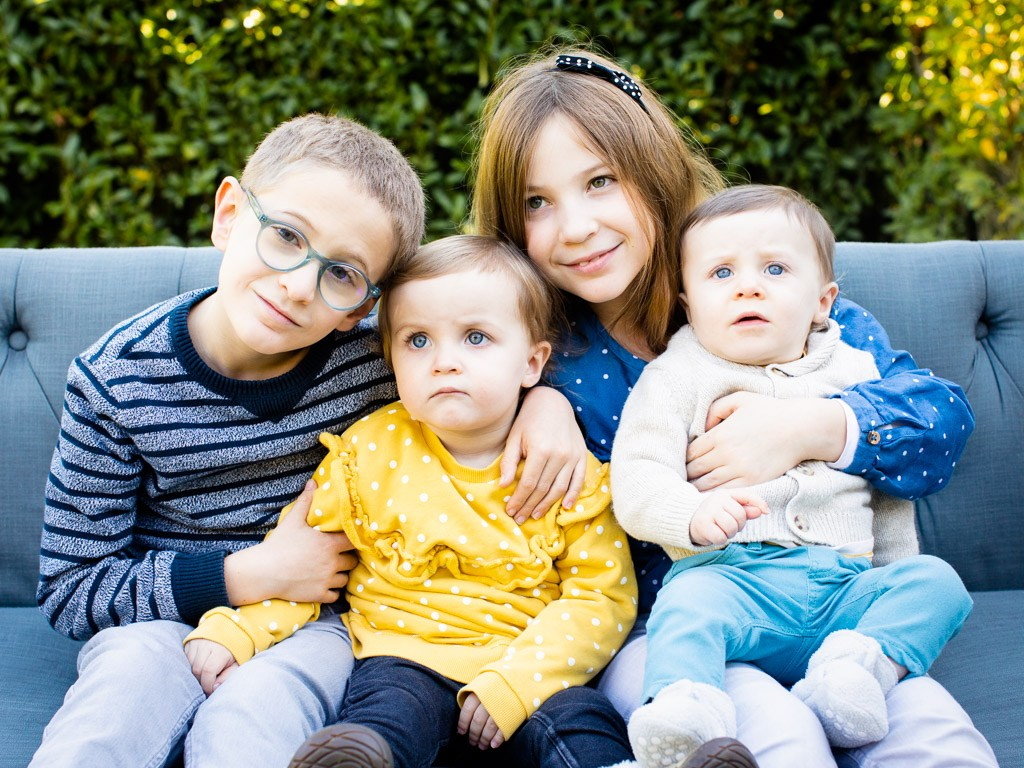 adorable group of four siblings cuddle together on the couch in vaud family photo shoot