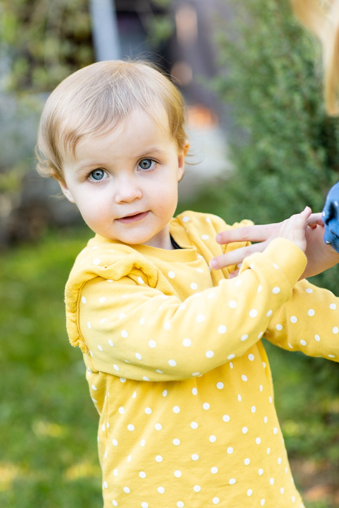 toddler plays outside in family garden photo session