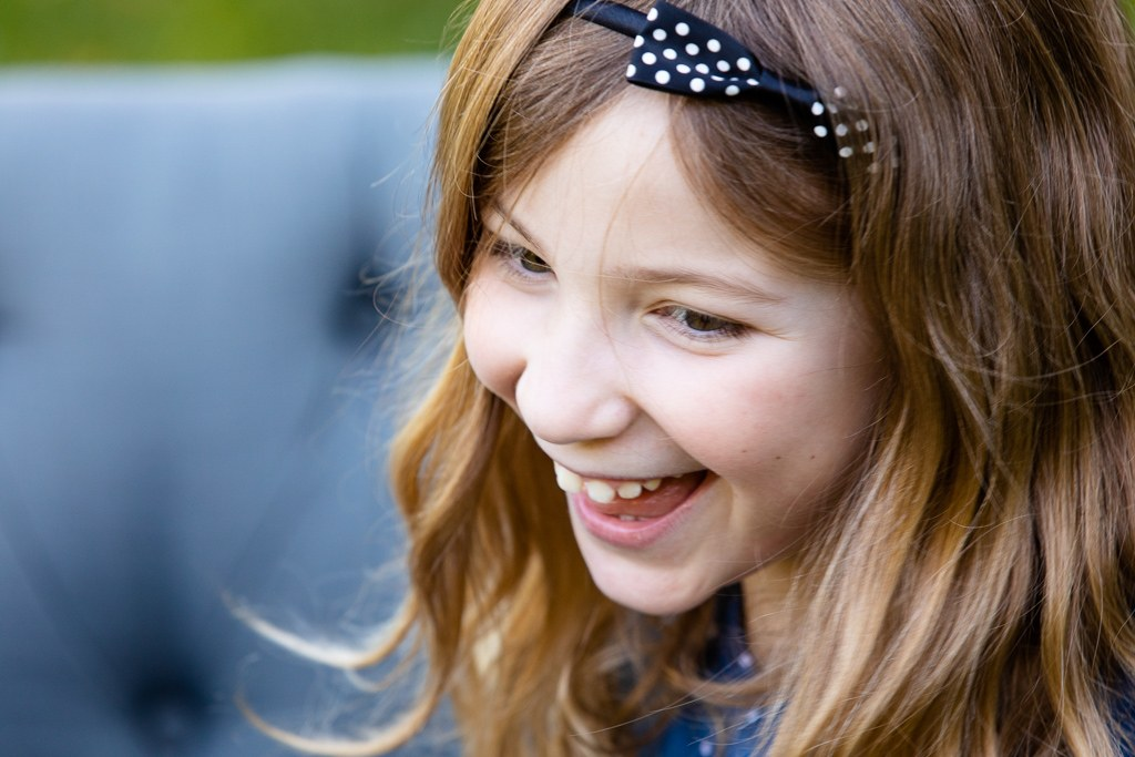 young girl laughs during backyard photo session