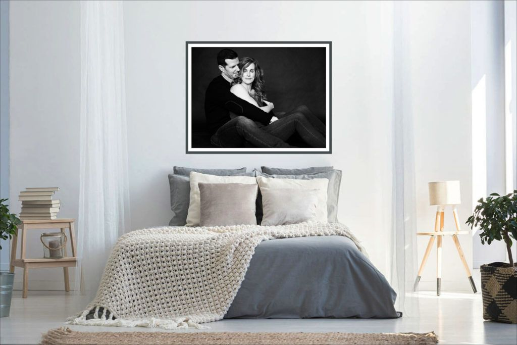 gorgeous black and white framed print of a couple on wall above bed